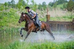 Eventer en caballo es supera el salto de agua Imagen de archivo libre de regalías