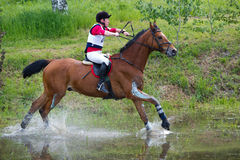 Eventer on horse is overcomes the Water jump Stock Images
