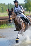 Eventer on horse is overcomes the Water jump Stock Photography