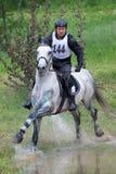 Eventer sur le cheval est surmonte le saut d'eau image stock