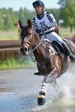 Eventer sur le cheval est surmonte le saut d'eau photographie stock