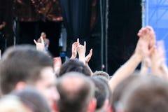 Evento do ar livre do concerto de rocha As mãos esticam e mostram chifres fotografia de stock