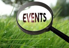 Events. Magnifying glass with the word events on grass background. Selective focus royalty free stock images