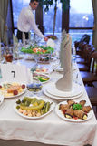 Events preparation for dinner. Table appointmant, unrecognizable waiters on background Royalty Free Stock Image