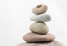 In evenwicht brengende die stenen op witte achtergrond worden geïsoleerd Stock Foto