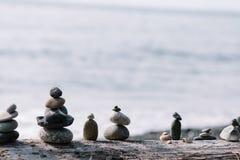 In evenwicht brengende rotsen op elkaar bij het strand stock fotografie