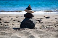 In evenwicht brengende stenensamenstelling op het strand met de blauwe oceaanachtergrondafbeelding stock foto
