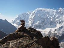 Evenwichtige stapel stenen tegen vaag higland meer als achtergrond en sneeuwbergen royalty-vrije stock fotografie