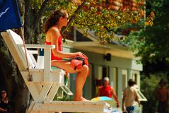 Ever Vigilant lifeguard. A young female lifeguard watches over swimmers at Walden Pond in Concord, Massachusetts royalty free stock image