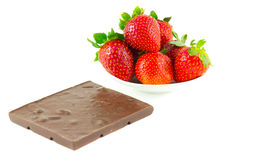 Everal strawberries on a saucer and a chocolate. Bar on a white background Royalty Free Stock Images