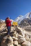 Everest Base Camp sign. A woman at Everest Base Camp sign, blue sky behind Stock Image
