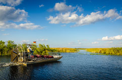 Everglades Airboat - Florida. Airboat hovers into path between grass on river in the Florida Everglades royalty free stock image