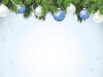 Evergreen with Blue Ornaments. Evergreen branches with silver and blue ornaments hanging from top. Copy space with faint snowflake and snow dot pattern Royalty Free Stock Image
