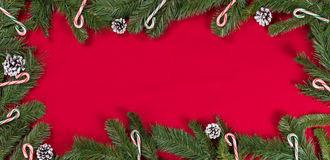 Evergreen branches and candy canes forming border on bright red Royalty Free Stock Image