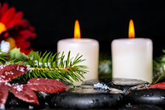 Evergreen branches with drops, leaves,  snow, candles and chrysa Stock Photos