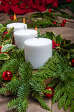 Evergreen Christmas centerpiece with white candles and poinsetti Royalty Free Stock Photography