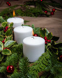 Evergreen Christmas centerpiece with white candles Stock Photo