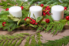 Evergreen Christmas centerpiece with white candles Stock Images