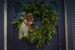 Evergreen Christmas wreath on purple door. Christmas wreath with decorative ribbon hanging from a purple door royalty free stock photo