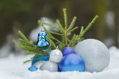 Evergreen sapling tree on snowy ground with Christmas silver and blue ornaments at bottom Royalty Free Stock Photos