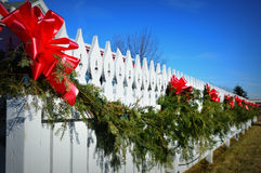 Evergreen Swag on White Picket Fence. A Christmas Evergreen swag on a white picket fence with red bows and a bright blue sky. Lake Geneva, Wisconsin Stock Photos