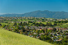 Evergreen Valley in spring. Lush green Evergreen Valley residential area in spring time with grass slope foreground and mountain and blue sky background Stock Photography