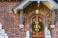 Evergreen Wreath on a Solid Oak Door with Small Orange and White Pumpkin Gourds. Deep in the woods stands this picturesque brick with accents of flat white Royalty Free Stock Photography