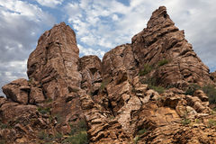 Evergreens grow from rocky mountainside. Juniper and mesquite plants grow in the cracks of the craggy mountains and cliffs of Tonto National Forest in eastern stock photo
