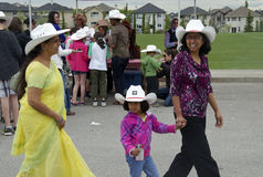 Every Culture Enjoys the Calgary Stampede. Three generations of ladies enjoy a morning of fun at a community pancake breakfast to celebrate the Calgary Stampede Royalty Free Stock Photo