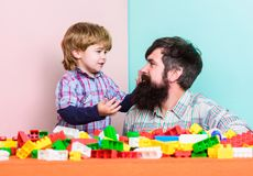Every dad and son must do together. Dad and kid build plastic blocks. Child care development and upbringing. Father son. Game. Father and son create stock photography