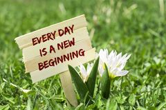 Every day is a new beginning. On wooden sign in garden with white spring flower Royalty Free Stock Image