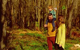 Every day a new discovery. Mother and father piggybacking little son hiking in woods, discovery concept. Family on stock images