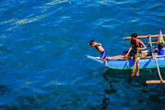 Every dive is worth a penny. Poverty stricken family in mindoro philippines earns a living by waiting for passenger ferries and begs for customers to throw money Royalty Free Stock Photos