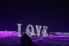 Coloured lights embrace under love stock image