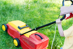 Every little help counts: image of electric grass trimming or lawn mover machine operating or pushing by small boy or girl Stock Photo