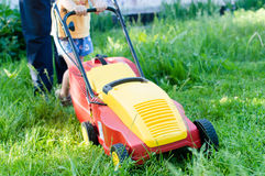 Every little help counts: image of grass trimming or lawn mover machine operating or pushing by small boy or girl and adult behind Stock Photo