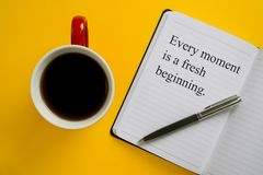 Notebook with inspirational quote with pen and coffee mug. Every Moment is a Fresh Beginning. Every moment is a fresh beginning. Inspirational quote on notebook Stock Image