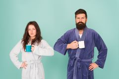 Every morning begins with coffee. Couple in bathrobes with mugs. Breakfast concept. Man with beard and sleepy woman. Every morning begins with coffee. Couple in royalty free stock images