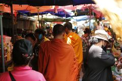 Buddhist monk in south east asia. Every morning the buddhist monks with their orange togas roam the streets in search of their meal with the faithful in exchange Stock Photo