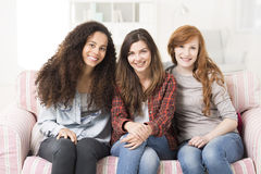 Every place is perfect with her best friends. Portrait of three girl friends sitting on a sofa and smiling at the camera Stock Images