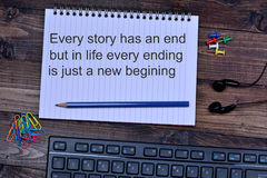 Every story has an end but in life every ending is just a new begining. On notebook Royalty Free Stock Photo