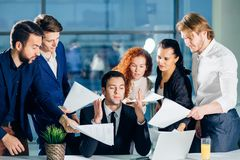 Everybody is looking at engineer and hold documents. man think and ignore them. Everybody is looking at engineer and hold documents. men think and ignore them Royalty Free Stock Photo