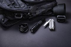 Everyday carry EDC items for men in black color - backpack, tactical belt, flashlight, watch and silver multi tool. Survival set. Minimal concept stock image