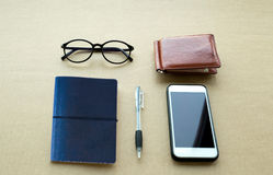 Everyday life object needs notebook  and pen ,cell phone and gla. Concept Everyday life object needs object notebook and pen ,cell phone and glasses on brown Royalty Free Stock Photo