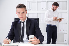 Everyday life in office. Serious businessman with smart phone is sitting in his chair. His colleague is making notes in clippad. Concept of everyday routine in Royalty Free Stock Photography