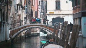 Everyday Life of Venice, Italy. Slow motion shot of people on the bridge over the water canal in Venice, Italy. Locals are crossing it, tourists are standing and stock video footage
