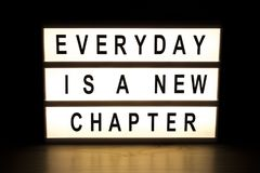 Everyday is a new chapter light box. Sign board on wooden table Royalty Free Stock Image