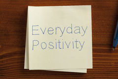 Everyday Positivity written on a note. Top view of Everyday Positivity written note on the wooden desk with pen aside stock photography