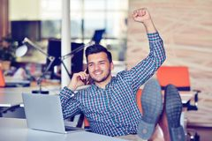 Cheerful young man in casual wear keeping arms raised and looking happy while sitting at the desk in office Royalty Free Stock Photography