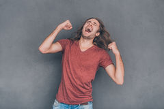 Everyday winner. Happy young man in casual wear standing against grey background and gesturing Royalty Free Stock Photo